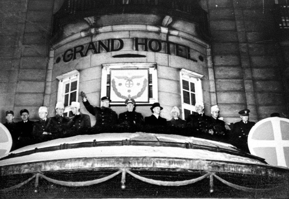 Fotografi av Quisling som vinker fra balkongen på Grand Hotel, sammen med uniformerte menn på begge sider. Nasjonal Samlings symboler preger balkongen